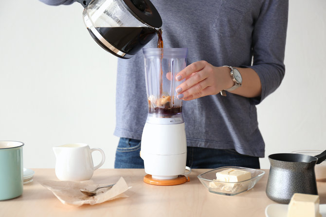 Woman using blender to make coffee with butter, closeup