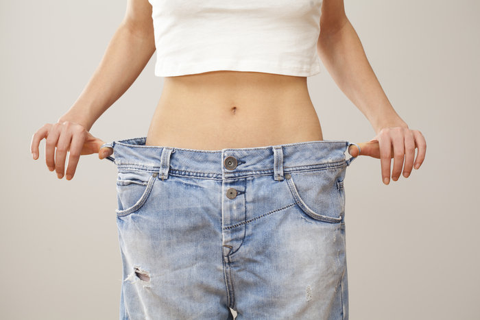Woman pulling the waistline of a pair of jeans to show weight loss