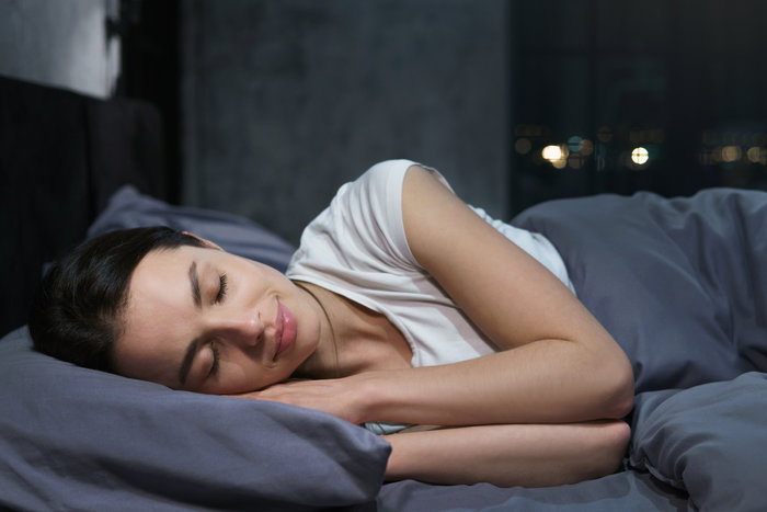 Young female sleeping peacefully in her bedroom at night, relaxing