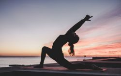 Woman practising yoga on a beach during sunset