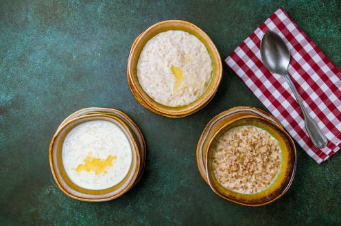 An overhead view of three bowls of porridge.