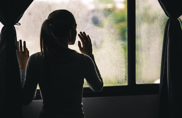 Young Lonely Woman Looking Out Through The Window of Her House During The Coronavirus Pandemic Quarantine Lockdown. Stay at Home