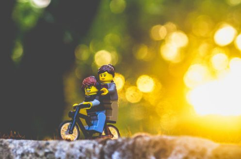 Two lego figures on a bicycle in woodland background.